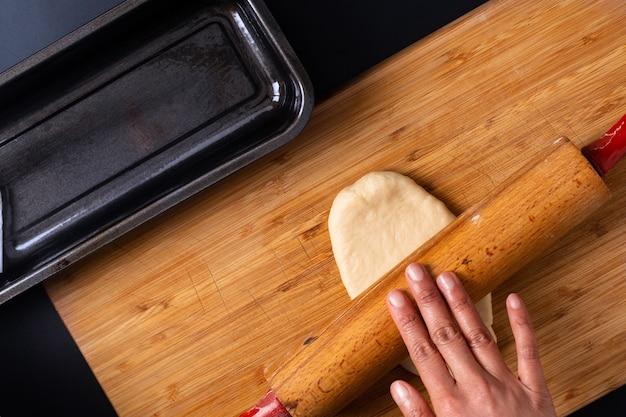Concepto para hornear alimentos hacer pan de pan de leche suave hecho en casa orgánico en una bandeja para pan en una tabla de madera Foto Premium