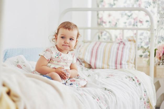 Concepto de infancia. niña en vestido lindo emplazamiento en la cama jugando con juguetes en el hogar. habitación infantil blanca vintage Foto Premium
