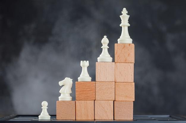 Concepto de jerarquía empresarial con figuras en pirámide de bloques de madera en niebla y vista lateral del tablero de ajedrez. Foto gratis