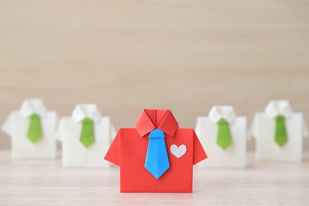 Concepto de liderazgo y trabajo en equipo, camisa roja de origami con corbata y líder entre pequeñas camisas en blanco Foto Premium