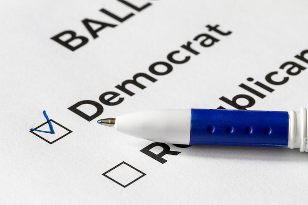 Concepto de lista de verificación primer plano de la papeleta con las palabras demócrata y republicano y una pluma en él. una marca de verificación para demócrata en la casilla de verificación. Foto Premium