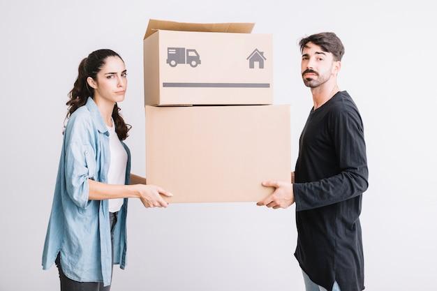 Concepto de mudanza con pareja llevando dos cajas Foto gratis