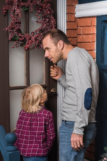 Concepto de navidad con padre tocando la puerta Foto gratis