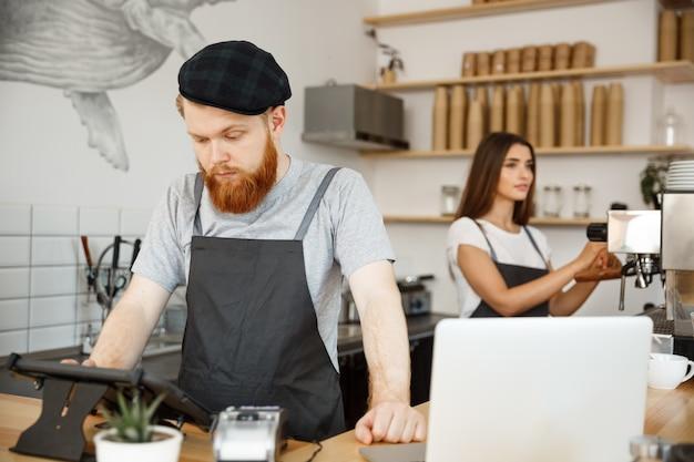 Concepto de negocio del café - el barman barbudo hermoso joven, el barista o el encargado que fijan la orden de huésped en menú digital de la tablilla en la cafetería moderna. Foto Premium