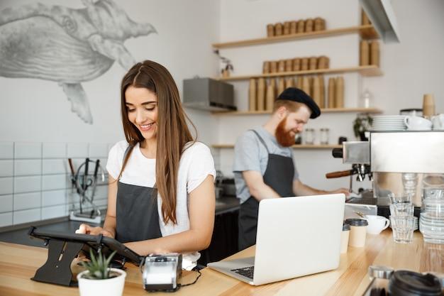 Concepto de negocio de café - caucásicos barista barista o gerente de postar orden en el menú de tableta digital en la cafetería moderna. Foto Premium