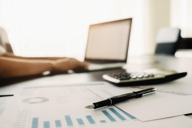Concepto de negocio con copia espacio. mesa de escritorio de oficina con enfoque de pluma y análisis de gráfico, computadora, bloc de notas, taza de café en el tablero desk.vintage retro filtro, enfoque selectivo. Foto gratis
