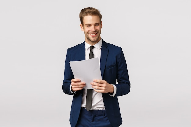 Concepto de negocio, elegancia y éxito. apuesto hombre de negocios moderno con estilo en traje clásico, corbata, documentos, papel y riendo, sonriendo, apartar la mirada, expresar confianza, fondo blanco. Foto Premium
