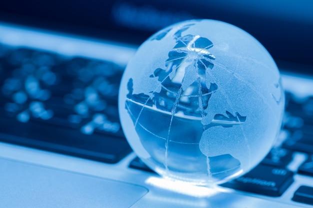 El concepto de negocio del mundo del vidrio en una computadora portátil Foto gratis