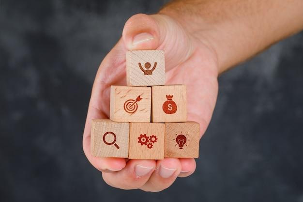 Concepto de negocio en vista lateral de la mesa gris sucio. mano sosteniendo bloques de madera con iconos. Foto gratis