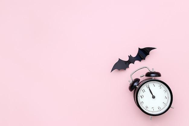 Concepto de noche de halloween. despertador negro y murciélago volador sobre fondo rosa. plano creativo, vista superior Foto Premium