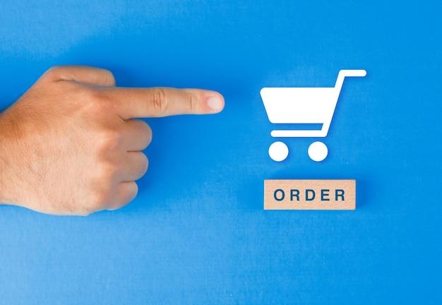 Concepto de pedido con bloque de madera, icono de la cesta de papel en la mesa azul plana. mano de hombre apuntando. Foto gratis