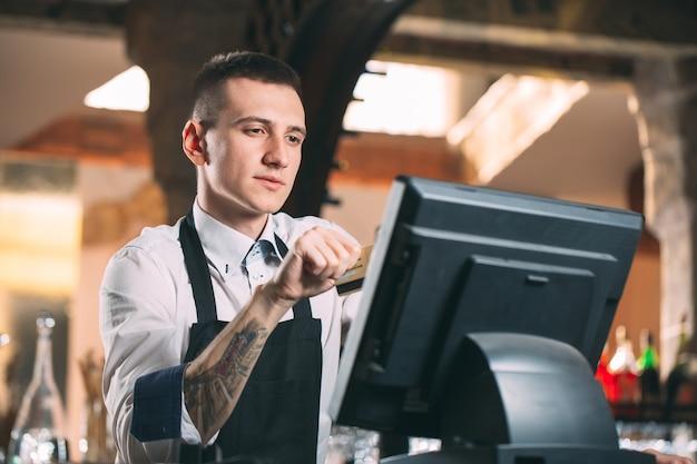 Concepto de pequeñas empresas, personas y servicios: hombre feliz o camarero en delantal en el mostrador con caja trabajando en el bar o cafetería Foto Premium