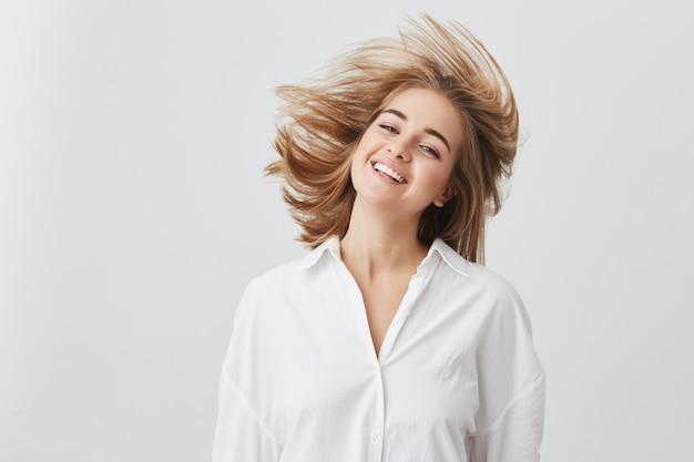 Concepto de personas, belleza y estilo de vida. foto de niña bonita rubia con una amplia sonrisa vestida con camisa blanca, saltando y jugando con su cabello. alegre y juguetona mujer caucásica. Foto gratis