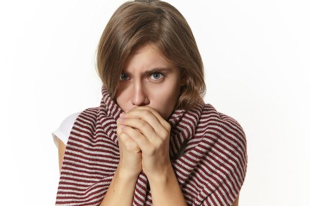 Concepto de personas, enfermedad y salud. primer plano de una mujer caucásica joven frustrada molesta que se siente fría, con una bufanda grande alrededor del cuello y los hombros, respirando con las manos para calentar Foto gratis