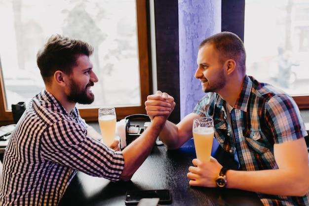 Concepto de personas, hombres, ocio, amistad y celebración: amigos varones felices bebiendo cerveza y peleando en el pub Foto Premium