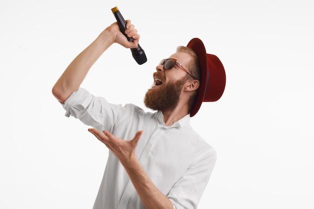 Concepto de personas, música, diversión, espectáculo y entretenimiento. artista pop pelirrojo elegante y guapo emocional con barba gruesa cantando en el micrófono con sombrero redondo rojo y tonos de moda Foto gratis