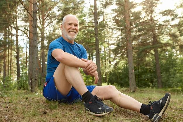 Concepto de personas, naturaleza, deportes y ocio. feliz hombre jubilado sin preocupaciones con barba gris sentado cómodamente en la hierba en el bosque de pinos, manteniendo el codo en la rodilla, descansando después del ejercicio cardiovascular al aire libre Foto gratis