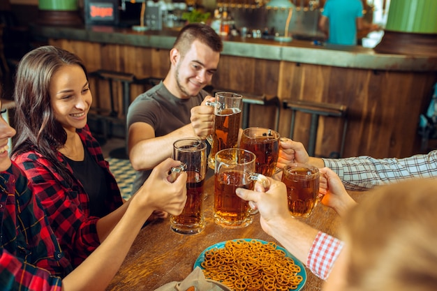 Concepto de personas, ocio, amistad y comunicación: amigos felices bebiendo cerveza, hablando y tintineando vasos en el bar o pub Foto gratis