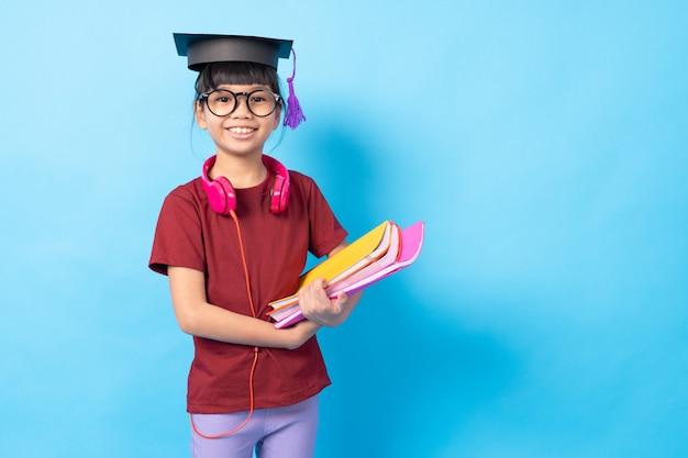 Concepto de posgrado y educación, estudiante de niña tailandesa de asia con libros y auriculares con sombrero de licenciatura Foto Premium
