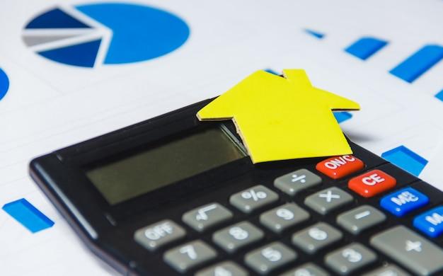Concepto de préstamos hipotecarios con casa de papel y calculadora sobre fondo blanco. Foto Premium