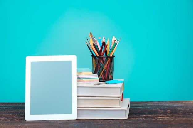Concepto de regreso a la escuela. libros, lapices de colores y laptop Foto gratis