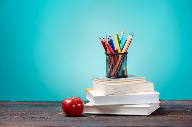 Concepto de regreso a la escuela. libros, lápices de colores y manzana. Foto gratis