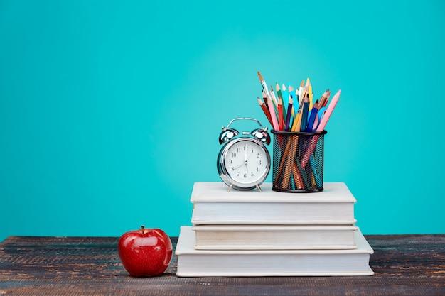 Concepto de regreso a la escuela. libros, lápices de colores y reloj. Foto gratis