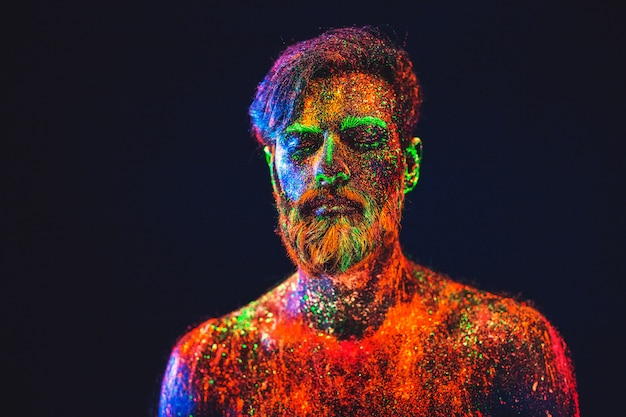 Concepto. retrato de un hombre barbudo. el hombre está pintado en polvo ultravioleta. Foto Premium