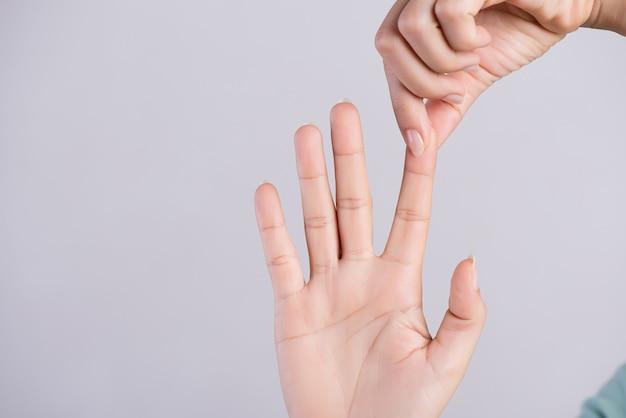 Concepto de salud y médico. mujer masajeando su dedo índice doloroso Foto Premium