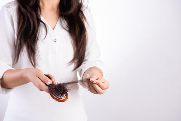 Concepto saludable mujer muestra su cepillo con cabello dañado de larga pérdida Foto Premium