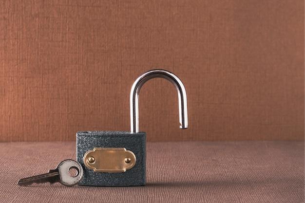 El concepto de seguridad de la información. sobre un fondo marrón claro, una cerradura abierta con una llave a su lado. Foto Premium