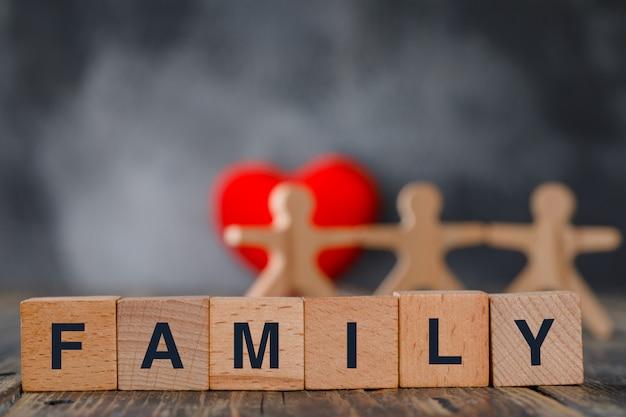 Concepto de seguro familiar con figuras de madera de personas, cubos, vista lateral de corazón rojo. Foto gratis