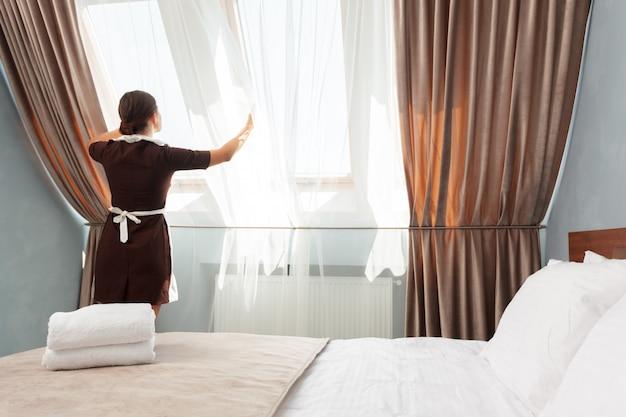 Concepto de servicio de hotel. camarera de ajuste de cortinas en la habitación. Foto Premium