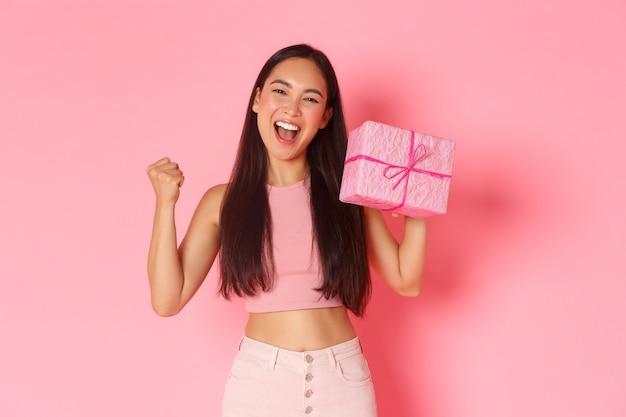 Concepto de vacaciones, celebración y estilo de vida. triunfando a la feliz cumpleañera asiática que parece optimista, le gusta recibir regalos, levantar la bomba de puño y mostrar el presente envuelto, de pie con un fondo rosa. Foto gratis