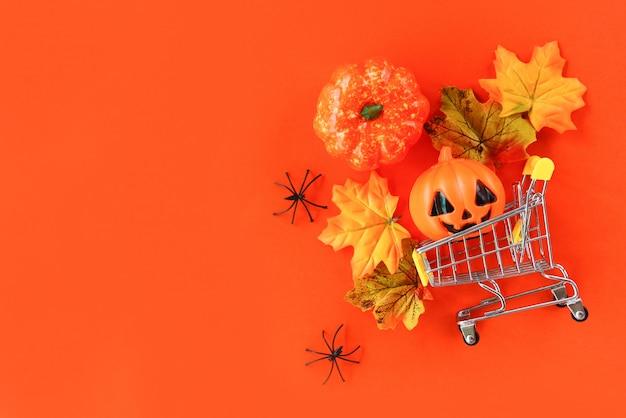 Concepto de vacaciones de compras de halloween / accesorios con araña calabaza jack o linterna y hojas de otoño en un carrito de compras en vista superior de fondo naranja Foto Premium