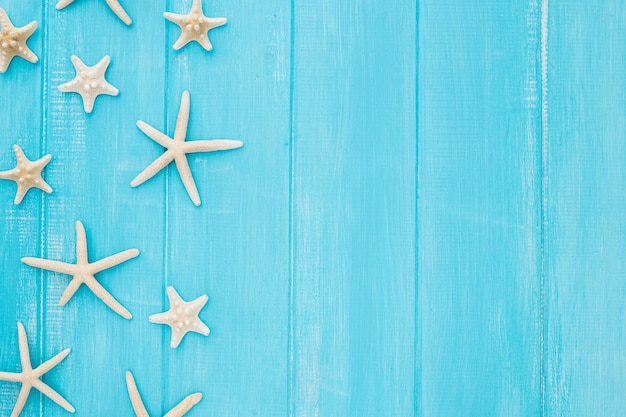 Concepto de verano con estrellas de mar sobre un fondo de madera azul con espacio de copia Foto gratis