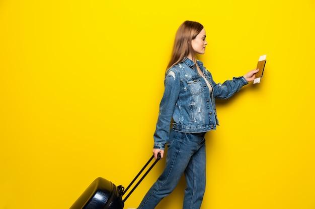 Concepto de viaje feliz mujer niña con maleta y pasaporte en pared de color amarillo Foto gratis