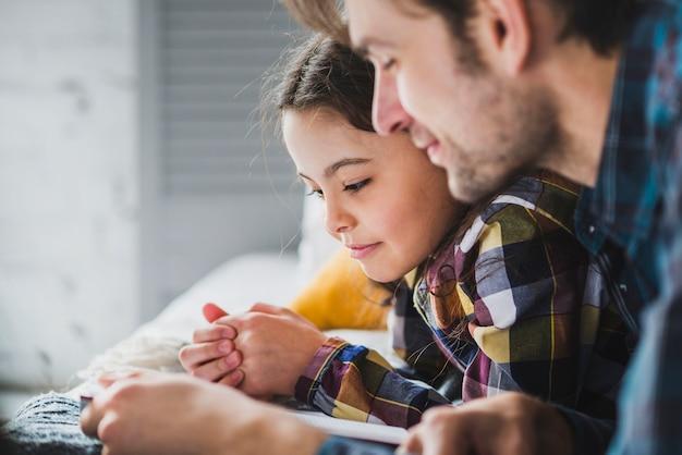 Concepto de vista de cerca para el día del padre con padre e hija leyendo Foto gratis