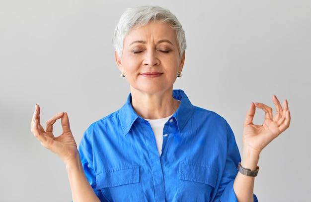 Concepto de zen, sabiduría, equilibrio y relajación. hermosa mujer de pelo gris de unos cincuenta años posando con los ojos cerrados meditando después de yoga conectando el pulgar y el dedo índice en gesto mudra Foto gratis