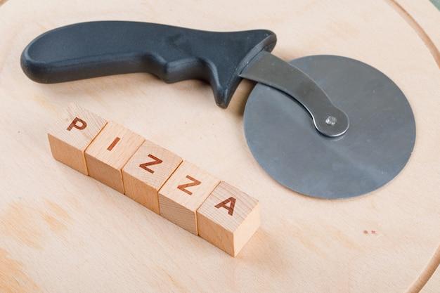 Conceptual de cocinar con bloques de madera con palabras, cortador de pizza. Foto gratis