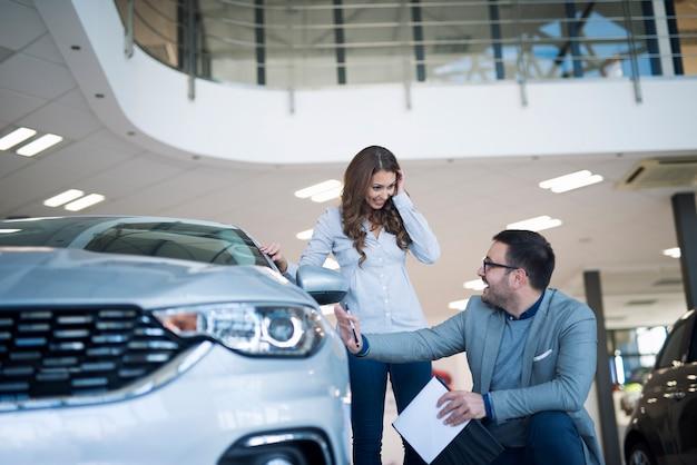 Concesionario de coches presentando coche nuevo al cliente Foto gratis