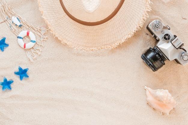 Concha de mar con sombrero de paja y cámara. Foto gratis