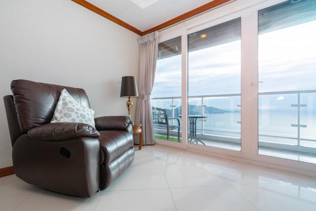 Condominio con vista al mar con sofá por el balcón. Foto Premium