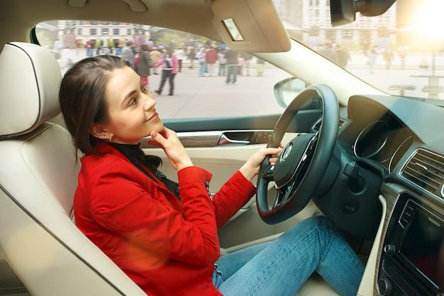 Conducir por la ciudad. mujer atractiva joven conduciendo un coche. joven modelo bastante caucásico en elegante chaqueta roja con estilo sentado en el interior del vehículo moderno. concepto de empresaria. Foto gratis