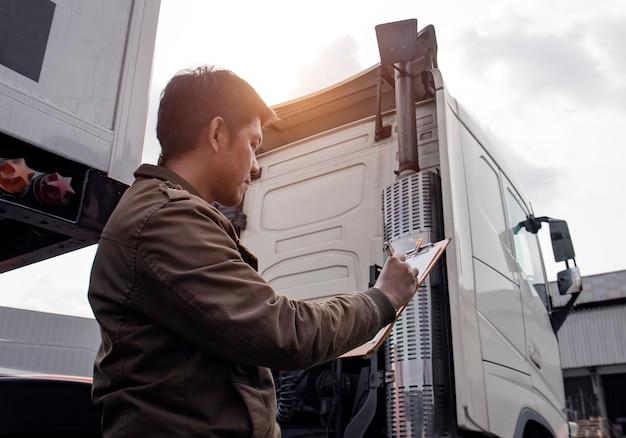 Conductor de camión asiático con portapapeles inspeccionando la lista de verificación de mantenimiento del vehículo de seguridad de semi camión moderno Foto Premium