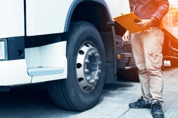 Conductor de camión que sostiene el tablero con la seguridad cheking del camión del neumático. Foto Premium