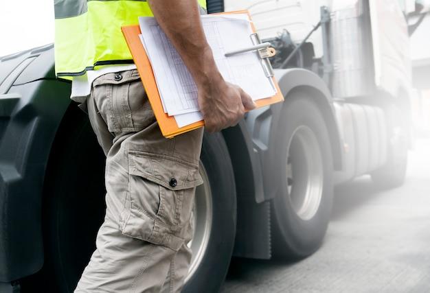 Conductor de camión está sosteniendo un portapapeles con un camión semi. Foto Premium