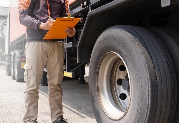 Conductor de camión está sosteniendo un portapapeles con la inspección de un neumático del camión Foto Premium