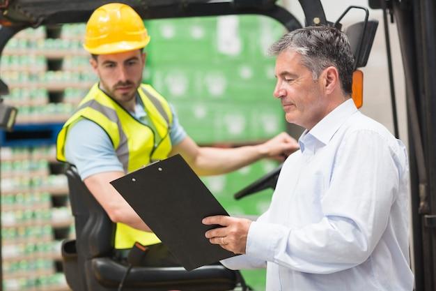 Conductor de carretilla elevadora hablando con su gerente Foto Premium