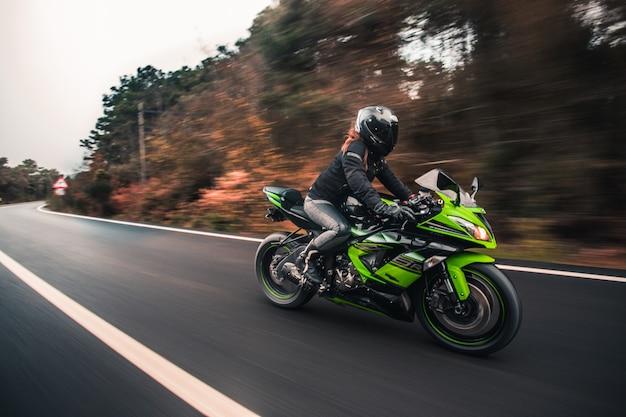 Un conductor femenino que conduce la motocicleta verde del color de neón en el camino. Foto gratis